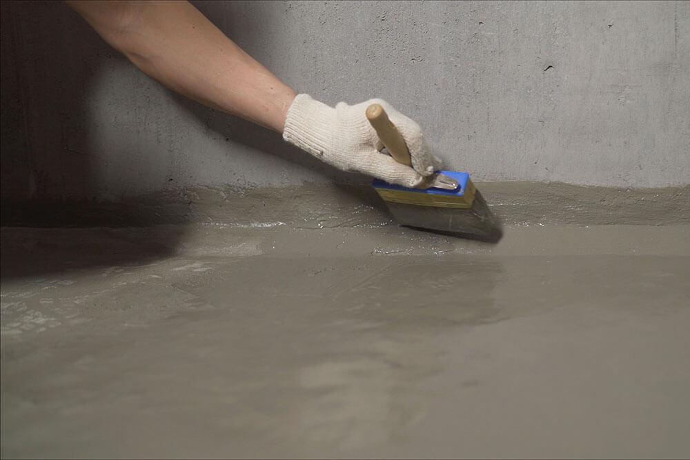 Painter painting a concrete floor