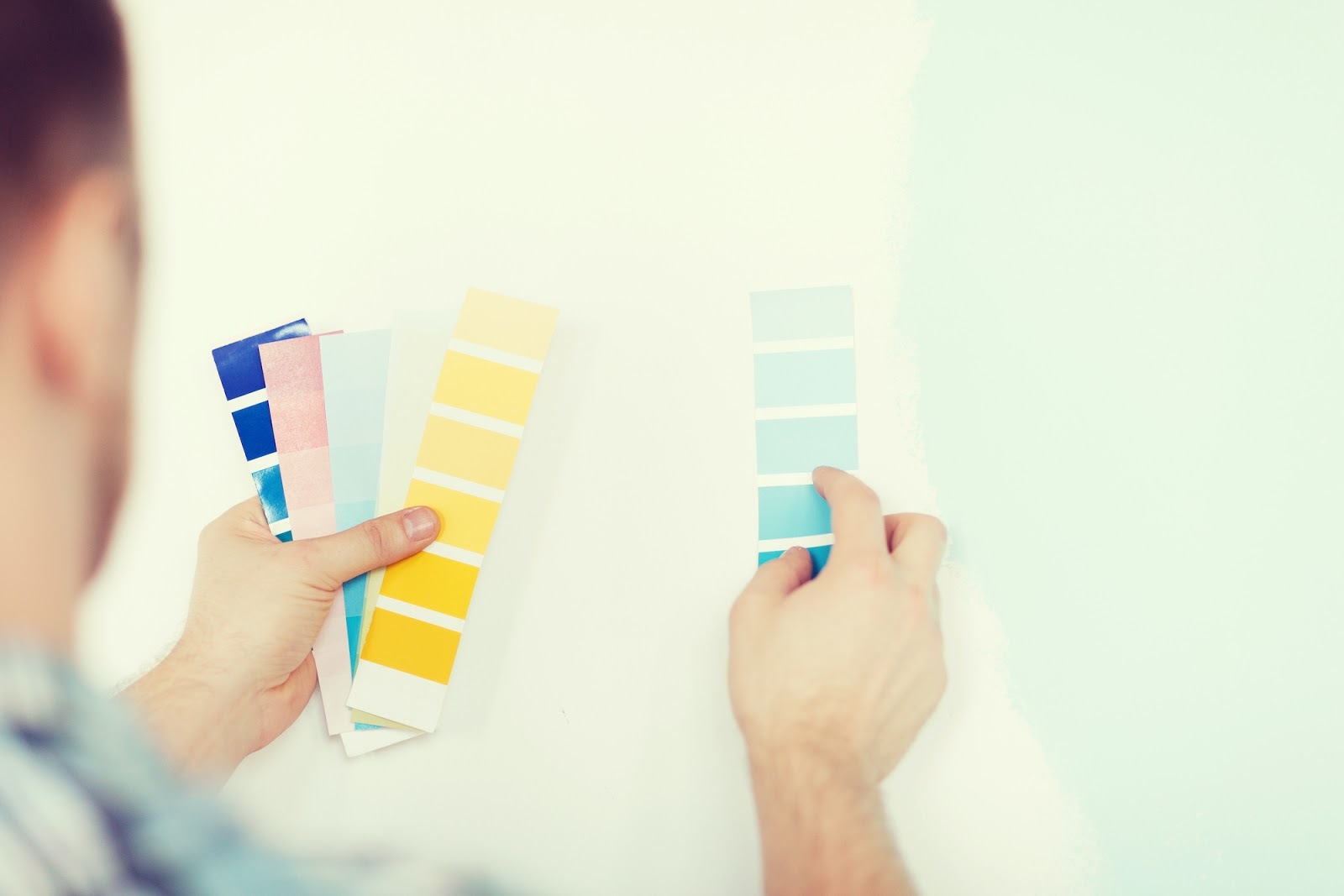 Man holding paint colors up to a wall