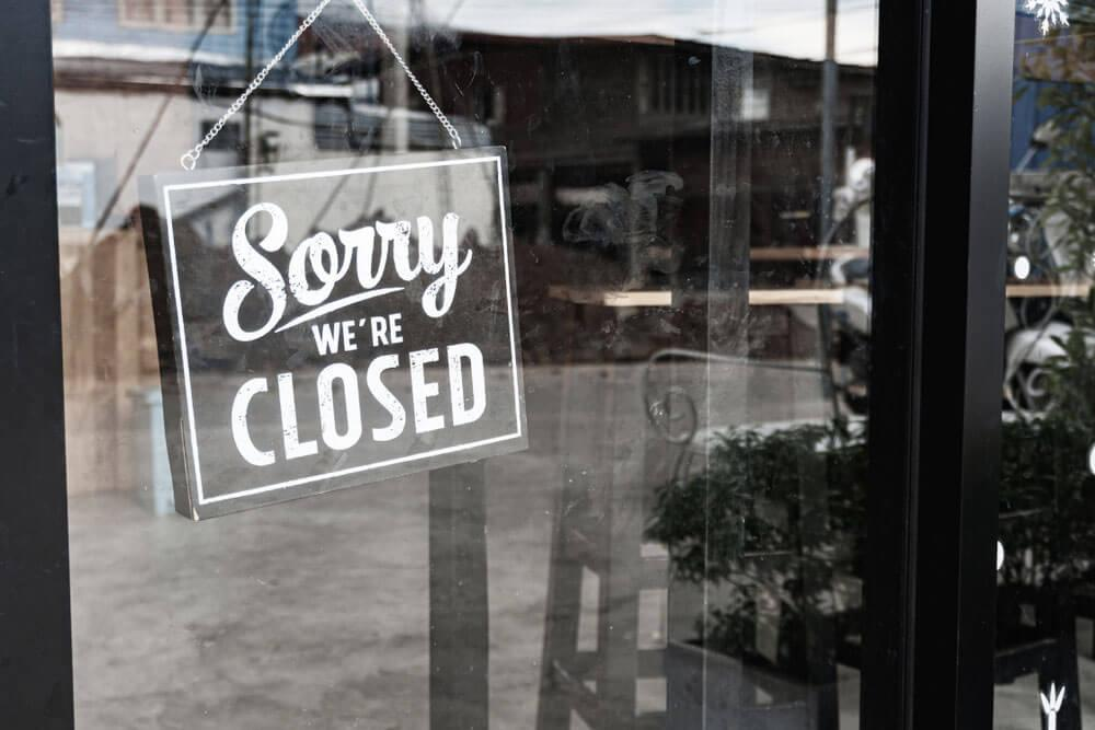 """Sign saying """"Sorry We're Closed"""" at a storefront"""
