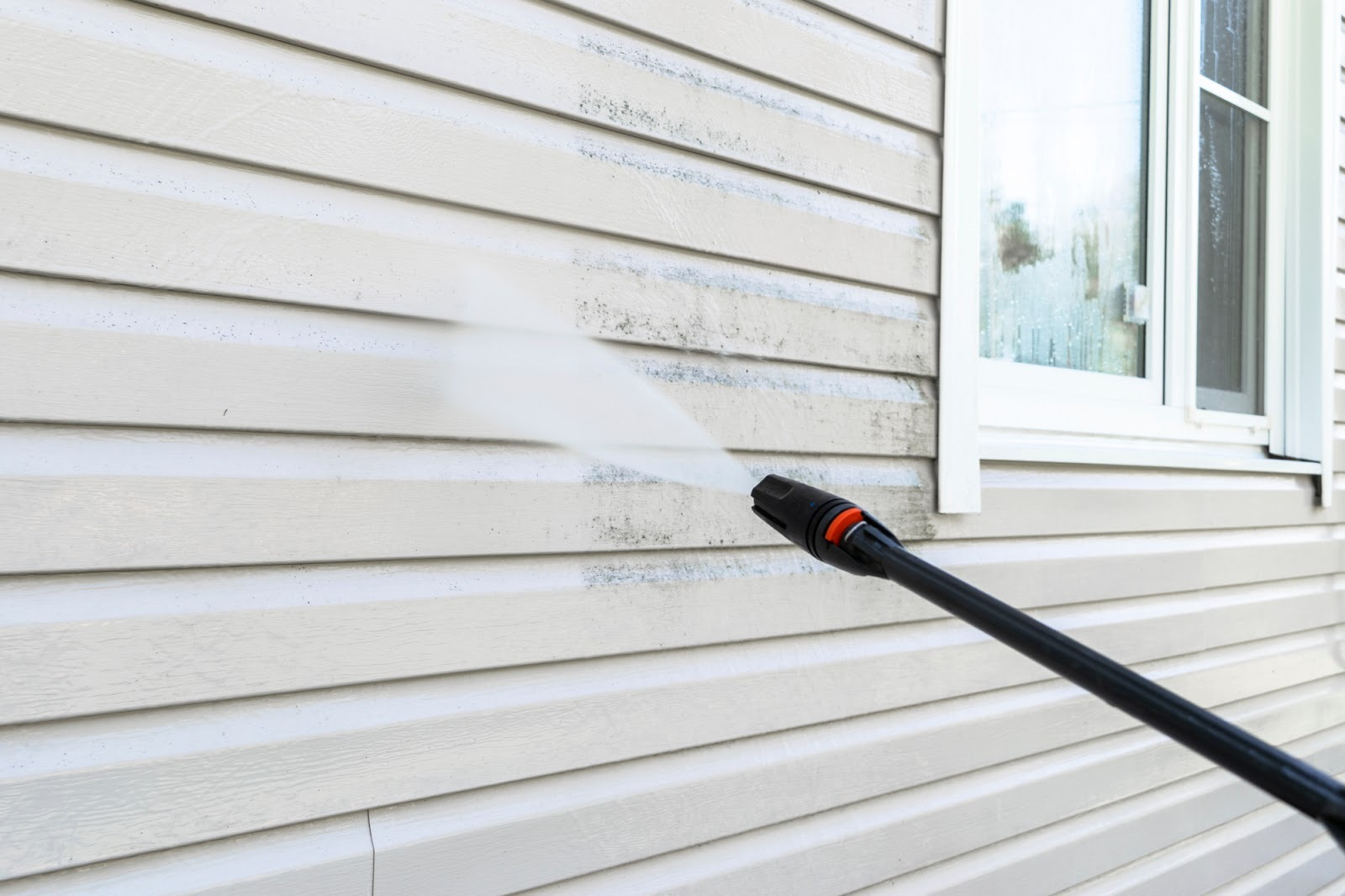 Power washer cleaning a home's siding