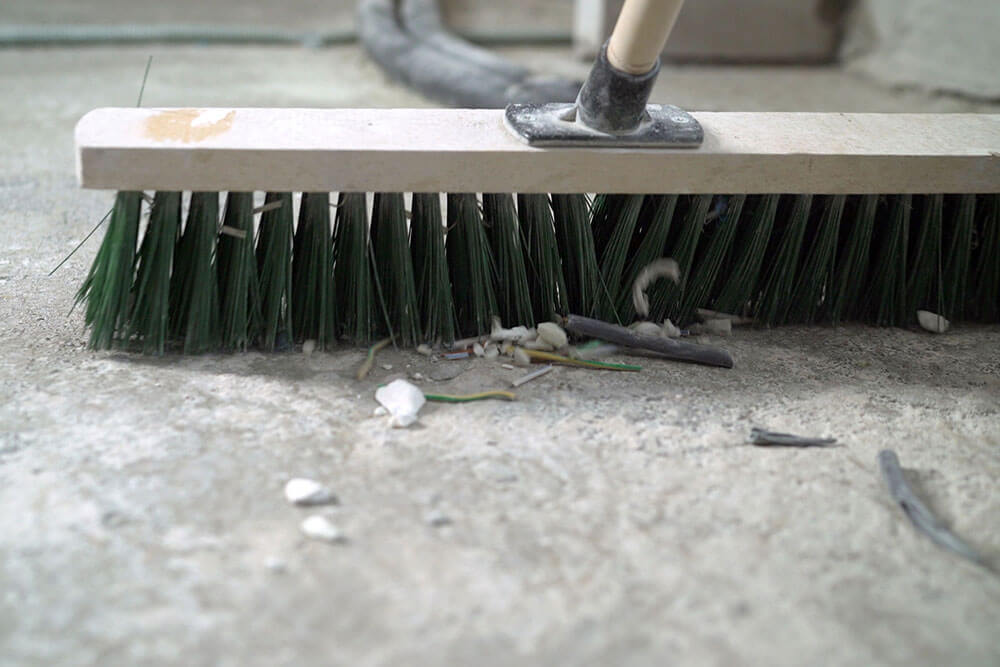 Person sweeping concrete floor before painting