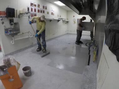 Contractor spreading polyurea flooring