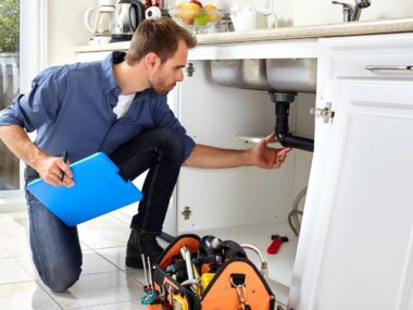 Realtor checking plumbing under a sink