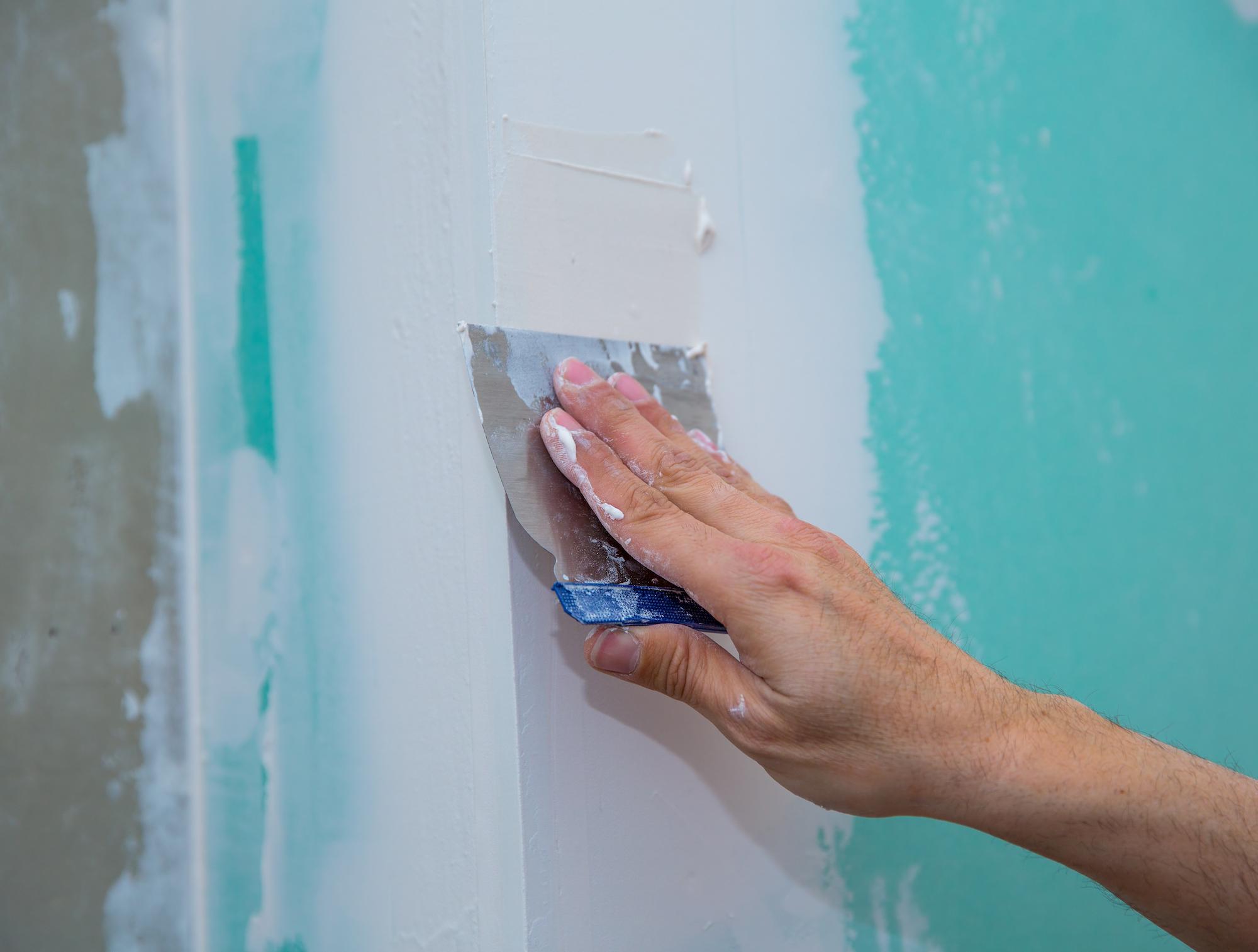 Person repairing damaged drywall
